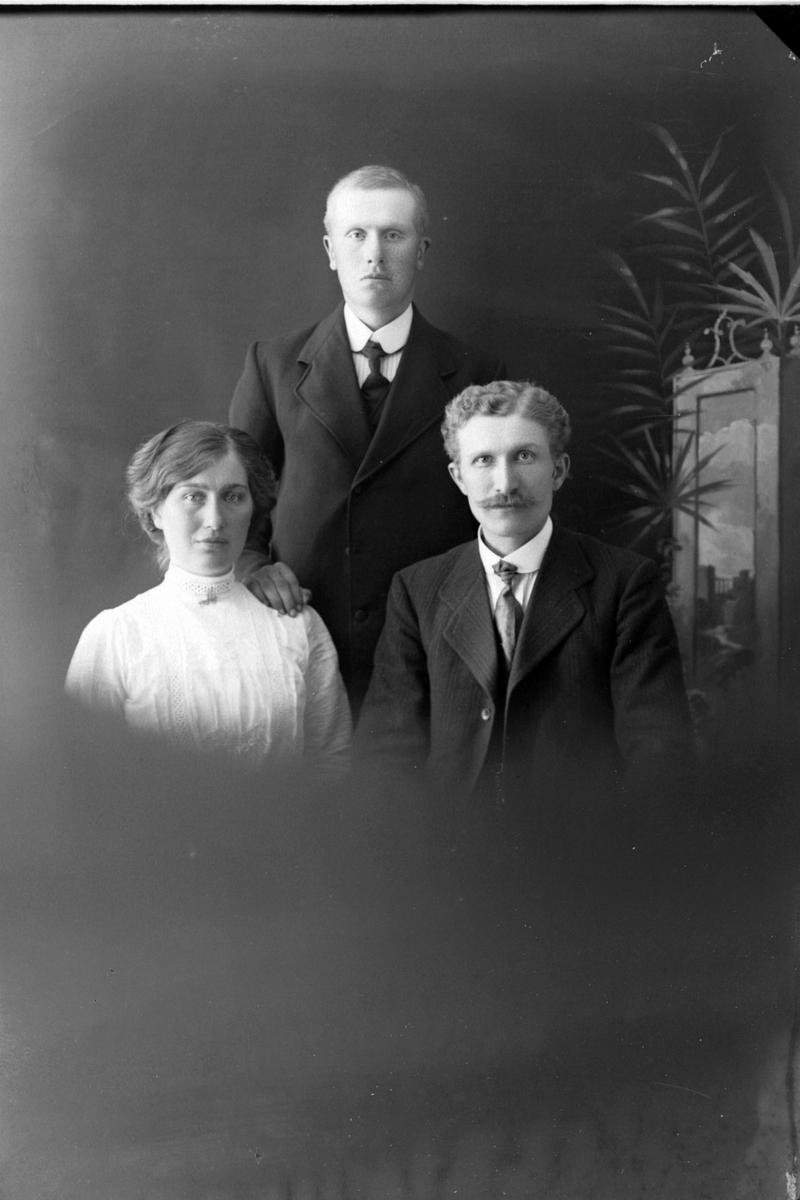 Studioportrett av tre personer i halvfigur.