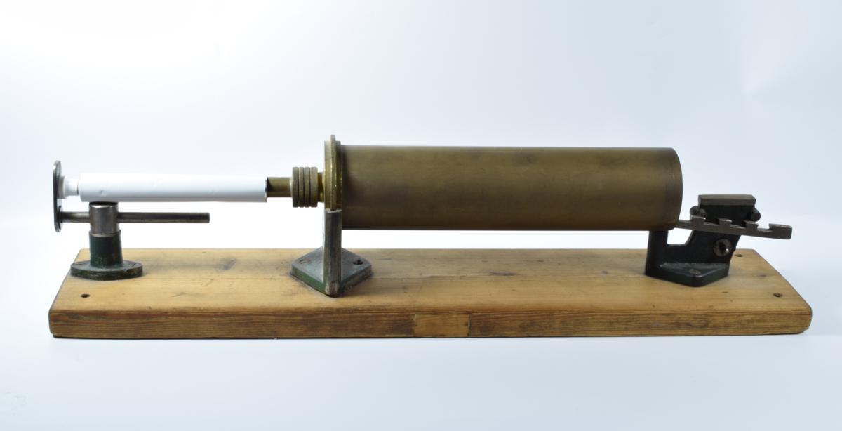 Tubefyllemaskin brukt til å fylle salve på tuber. Maskinen ble brukt når det skulle fylles et større antall tuber. Ved fylling av bare noen få tuber holdt at man benyttet en enkel tubesprøyte. Hoveddelen av maskinen består av en lang, liggende sylinder. Denne sylinderen ble fylt av salve som så ble presset inn i et mindre rør ved hjelp av et stempel og deretter inn i en metalltube som var tredd over røret. Tuben kunne så lukkes ved hjelp av en enkel tubelukker eller en tubelukkemaskin.   Sylinderen hviler på to grønnmalte metallføtter som er festet til en sokkel av tre.