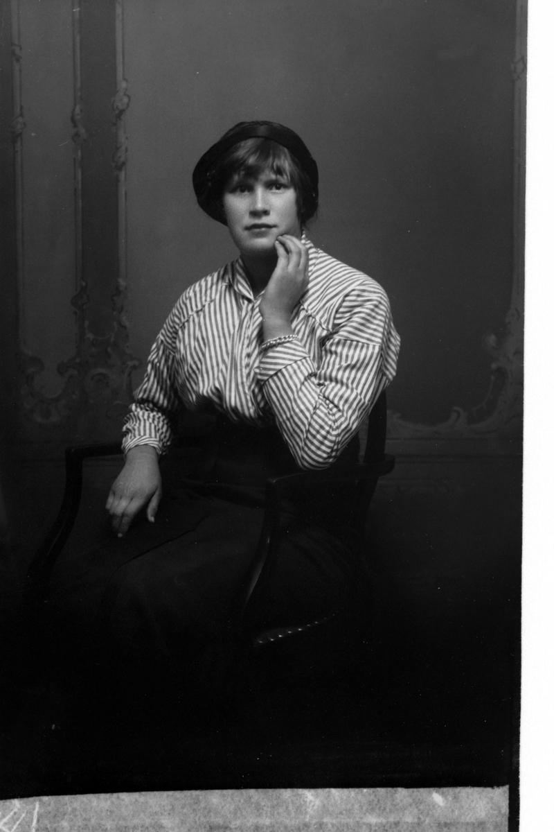 Studioportrett av en kvinne i en stripet skjorte.