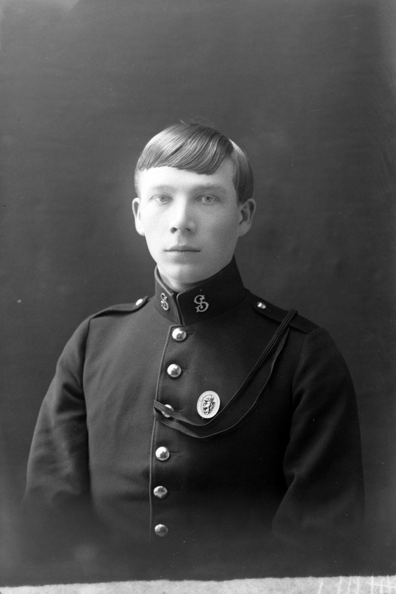 Studioportrett av en ung mann i uniform.