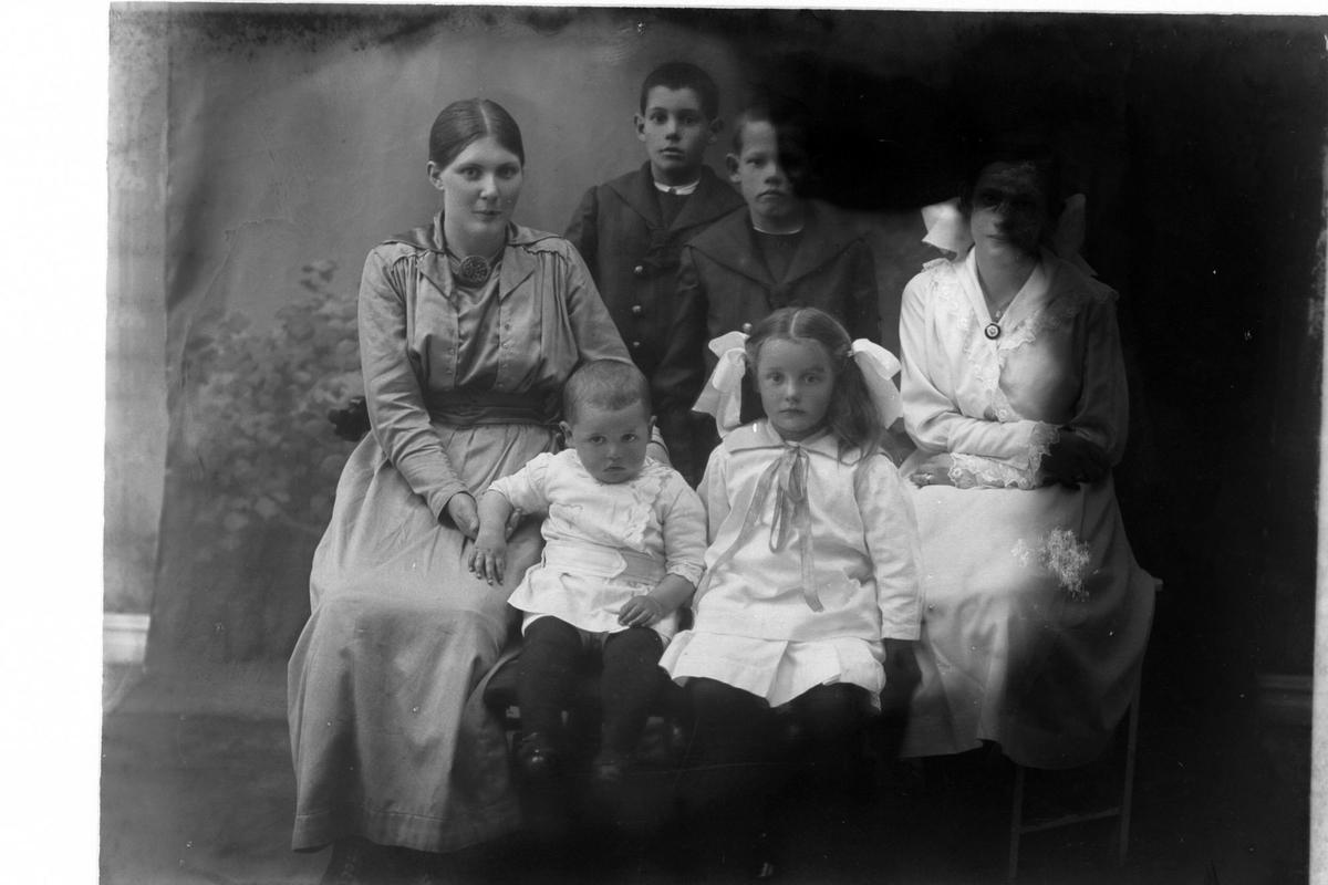 Studioportrett av to kvinner med fire barn. Bildet er delvis ødelagt.