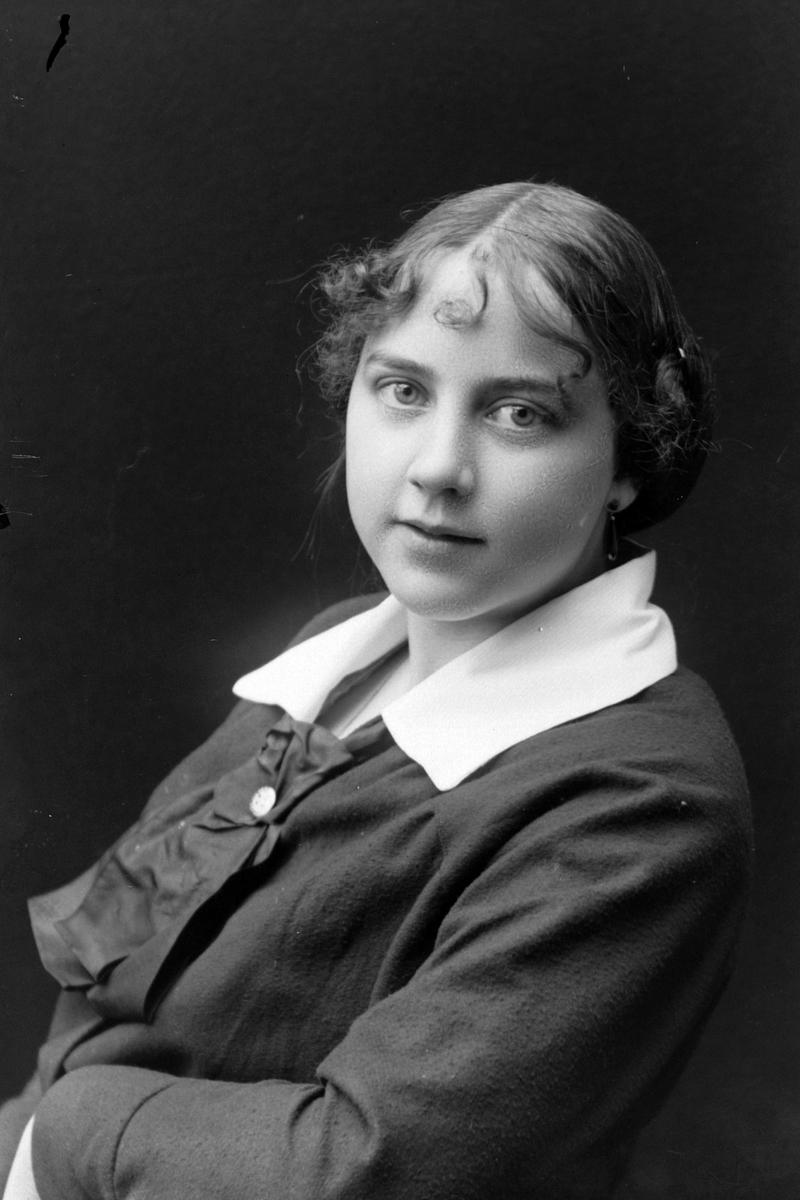 Studioportrett i halvfigur av en ung kvinne.