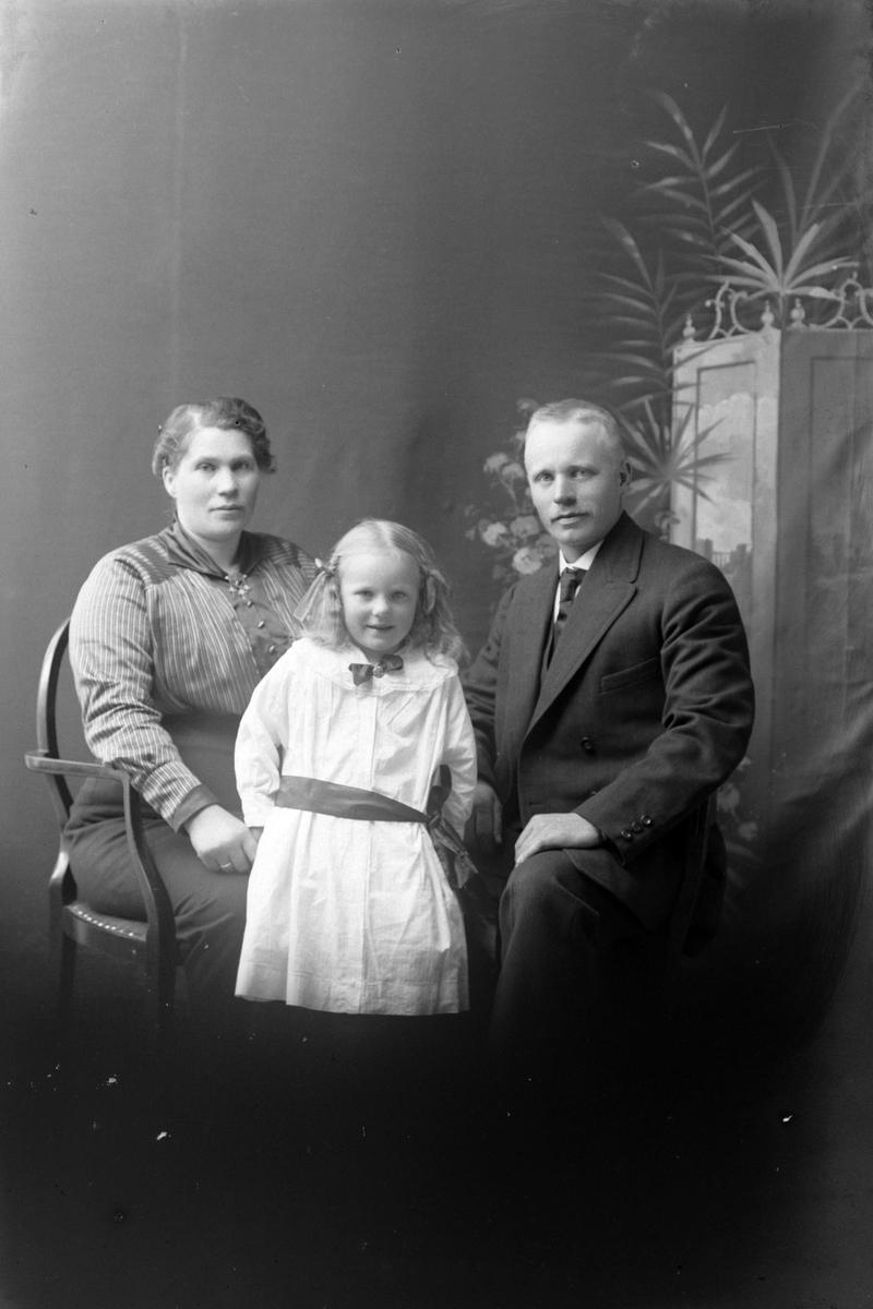 Studioportrett av en mann og kvinne med en jente imellom seg.