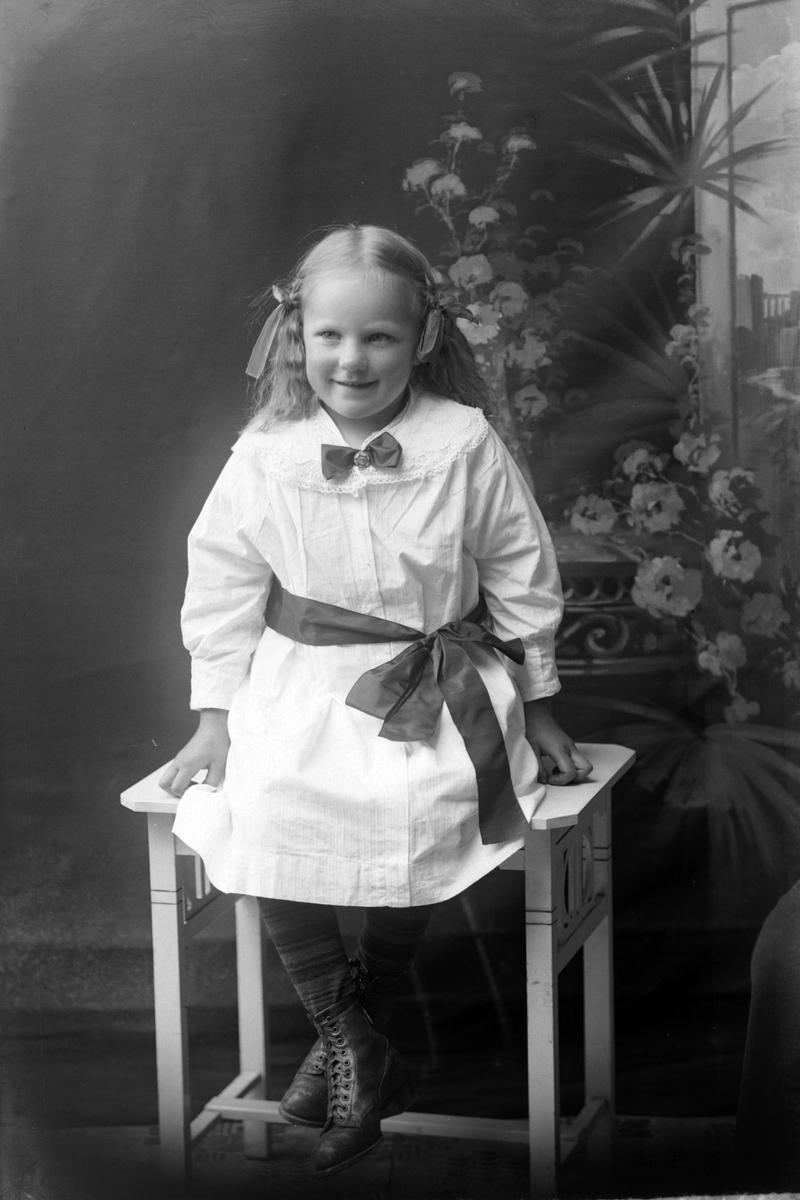 Studioportrett av en jente i hvit kjole med sløyfer i håret.