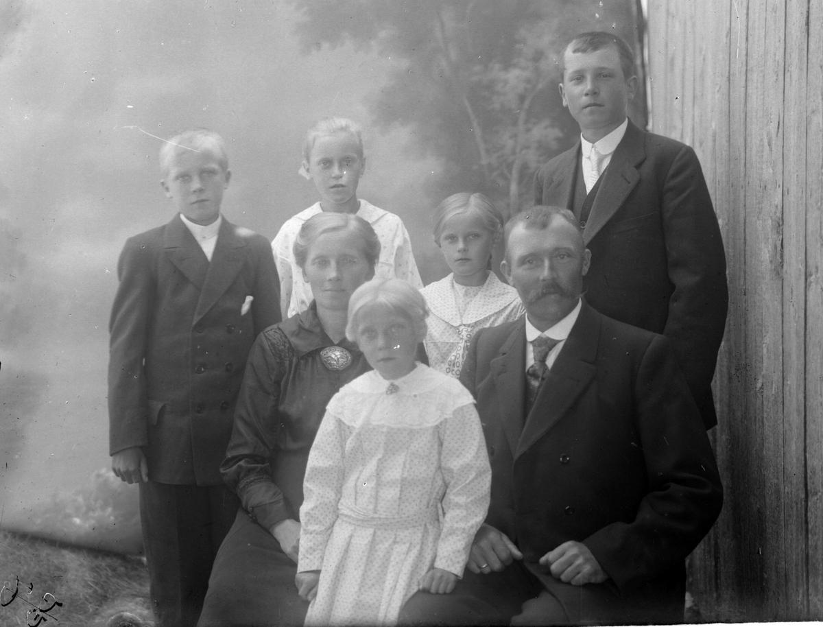 Studioportrett av en familie på syv i halvfigur, muligens familien Hellevik.