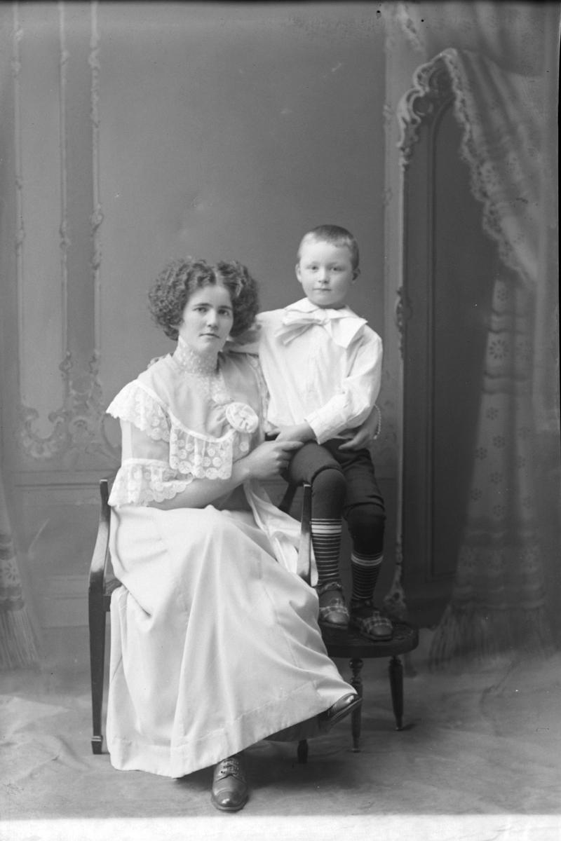 Studioportrett av en kvinne med en liten gutt ved siden av seg.
