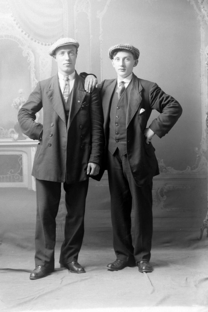 Studioportrett av to menn i helfigur.