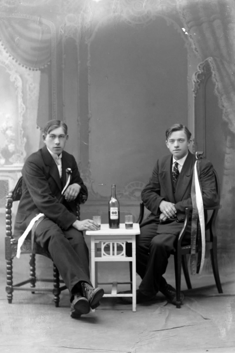 Studioportrett av to menn med store sløyfer. De sitter ved et bord og deler en flaske.