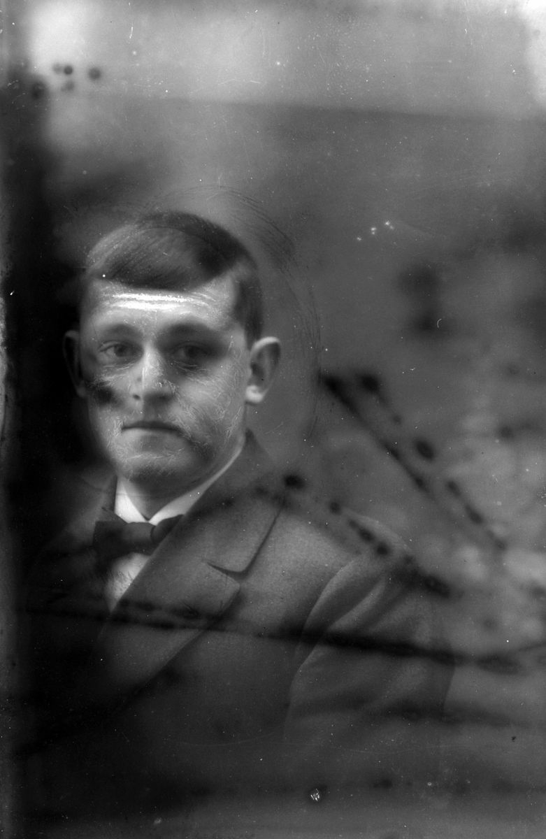 Studioportrett av en mann i halvfigur. Bildet er delvis ødelagt.
