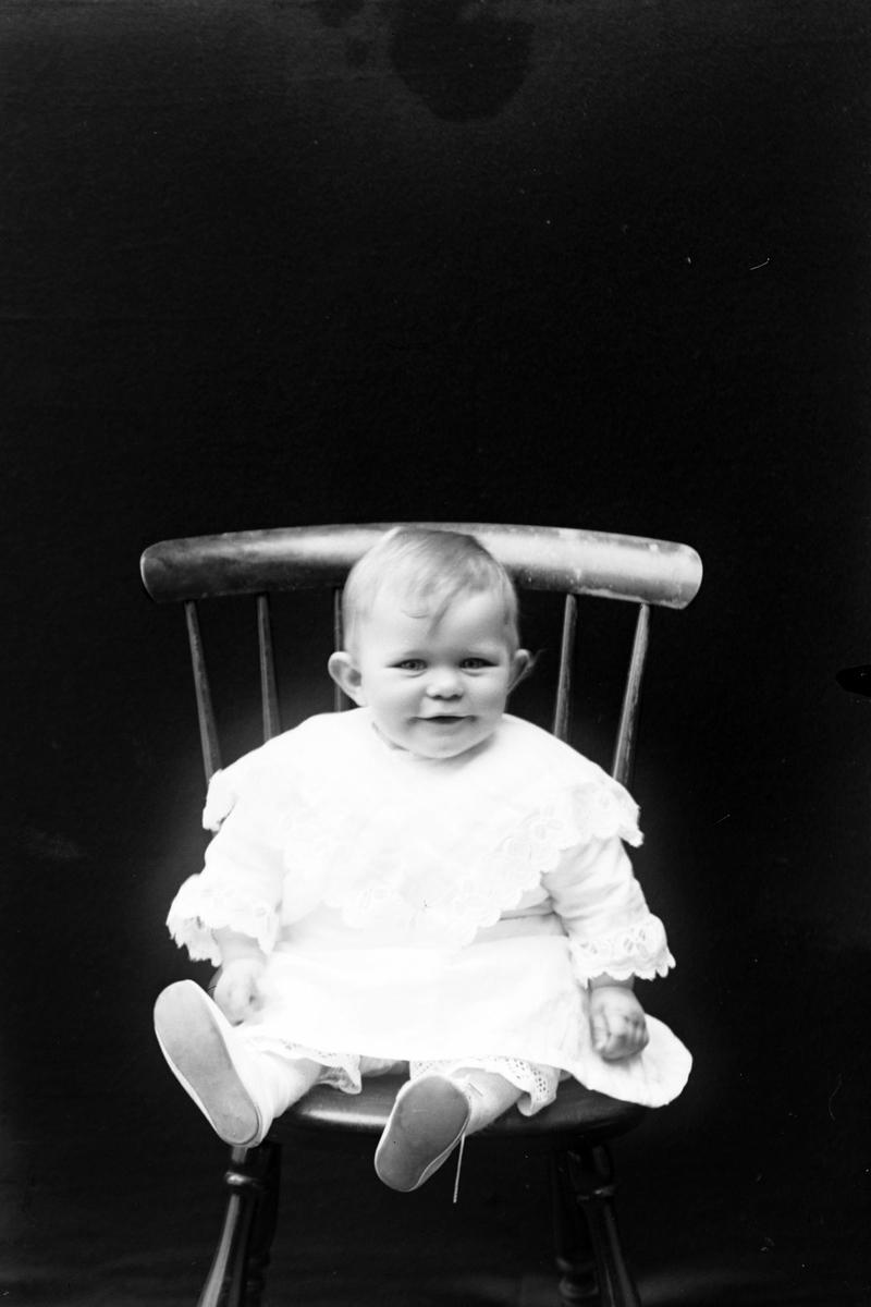 Studioportrett av et barn sittende på en stol.