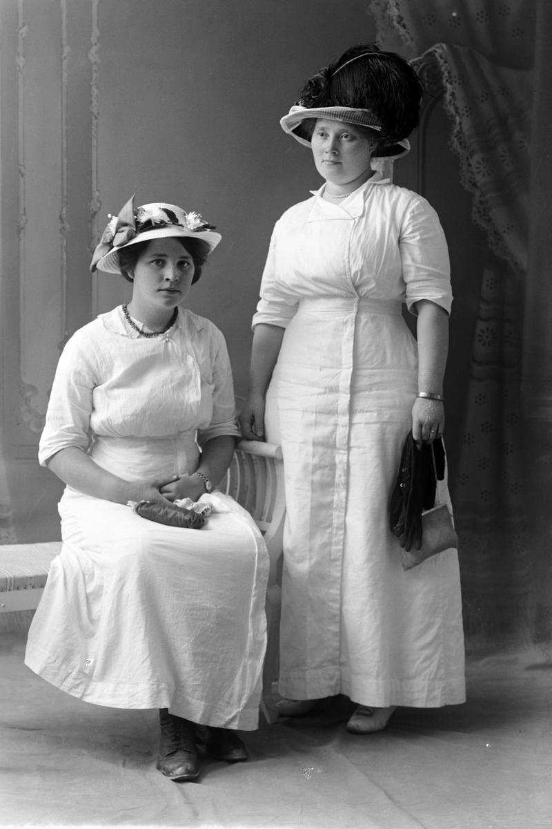 Studioportrett av to kvinner i hvite kjoler.