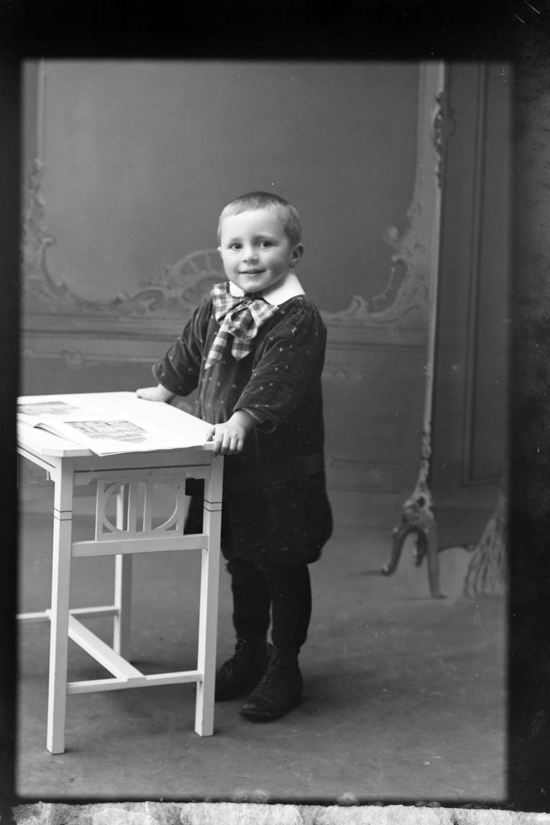 Studioportrett av en liten gutt i helfigur, muligens Evald Olsen.