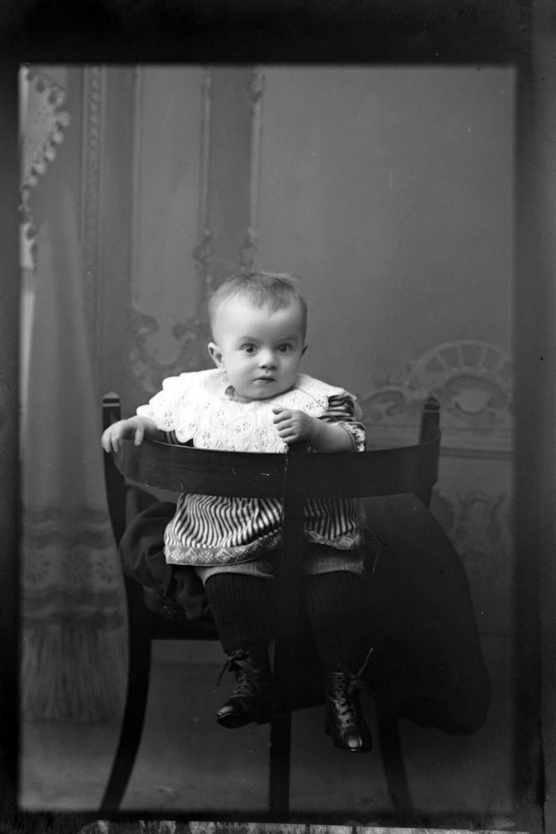 Studioportrett av et lite barn sittende på en stol.