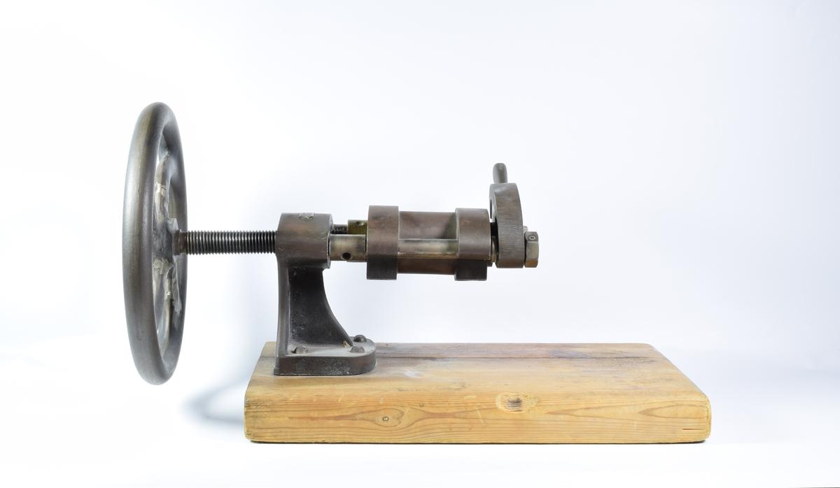 Maskin til å produsere tabletter. Maskinen er skrudd fast i en sokkel av tre.