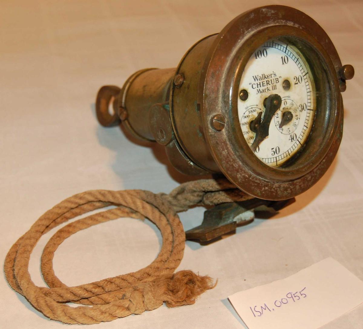 """Gjenstanden utgjer telleverket på ei """"Skipslogg/Distansemåler"""", og er den som viser den utseilte distanse. """"Prinsippet for en patentlogg er at en propeller som slepes gjennom vannet, gjør et visst antall omdreininger på ein viss distanse. Omdreiningenes antall registreres (telles opp) av et telleverk; dets inndeling er i nautiske mil (1850 meter). En komplett patentlogg består av rotatoren (propeller), logglinen, svinghjulet og telleverket. Telleverket har en stor viser, som går over en inndeling fra 0 - 100. Dessuten er det 2 mindre visere, hvorav den ene angir tiendedels (eller fjerdedels) nautisk mil. Den andre angir hundrer av nautiske mil. Svinghjulet er det som regulerer linens omdreining"""". Ref. Lærebok i Navigasjon. På """"Klokkehuset"""" er det inngravert: """"Use Walkers Solidified Oil"""", med en """"Pil"""" som angir skruretningen (""""Unscrew"""") på endelokket for tilkomst til smøring av drivverket. """"Klokka"""" er sylinderformet og er festet til ein leddbar """"fot"""". Festet på foten er tilpasset eit fundament. Fundamentet var som regel festet til rekkverket eller eit anna høveleg sted helt akterut på skipet/båten."""