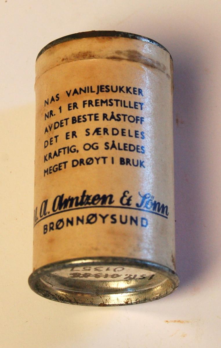 """Sylinderformet blekkboks med påklistret papiretikett med varedeklarasjon: """"NAS vaniljesukker Nr.1 er fremstillet av det beste råstoff. Det er særdeles kraftig, og således meget drøyt i bruk""""."""