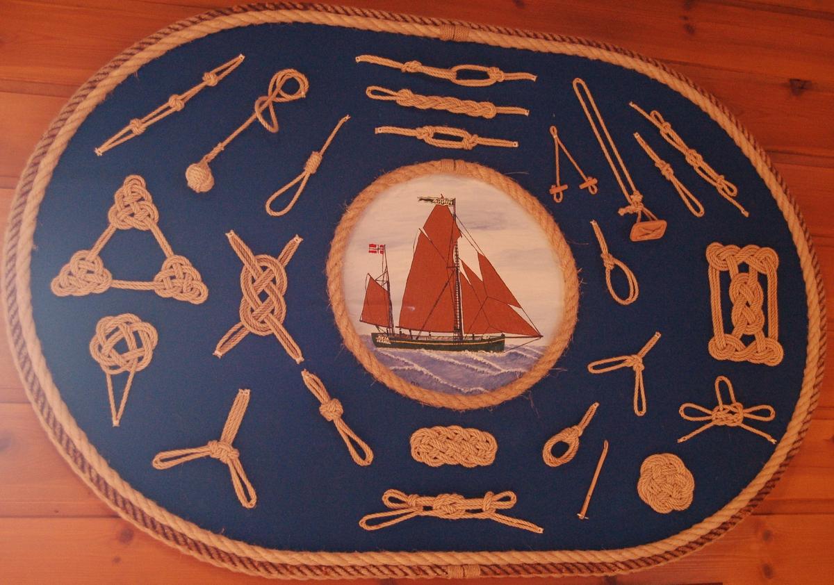 """Tavlen er en oval plate med forskellige tauknuter montert på en blå bakgrunn. I midten er der eit sirkelforma maleri av seglskuta """"Minna"""" innramet av manillatau."""