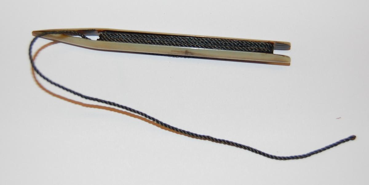 Nålen har en rektangulær form. I nålen er det utfreset et spor som tråden skal spoles opp på, og munnen på nålen er nebbformet med splittet ende. Nålen har påtredd bøtingstråd.
