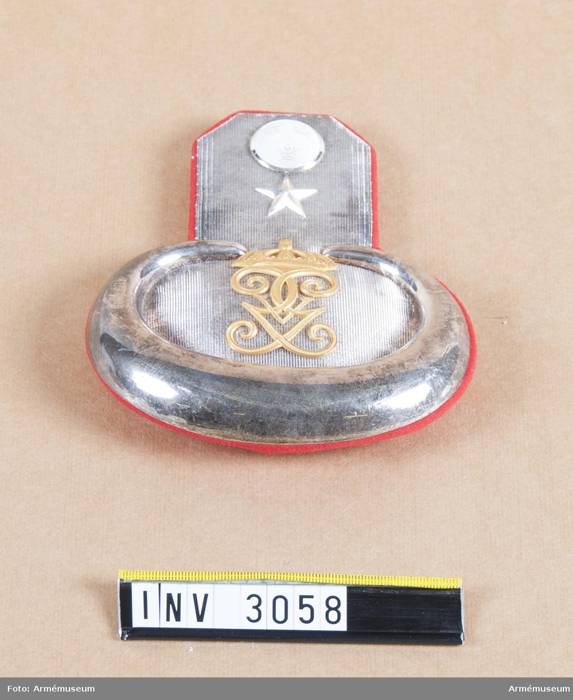 """Matta av vävt silverband med en silverplåt ytterst. Fodrad med rött kläde. H M Konungens namnchiffer, """"G V"""" m/1908 i guld, 60 mm högt. En stjärna=underlöjtnant, i silver betecknar reserven.  Överst en knapp av reg:s m/större i silver. På baksidan en hake, märkt MEA, att fästa vid axeln på vapenrocken."""