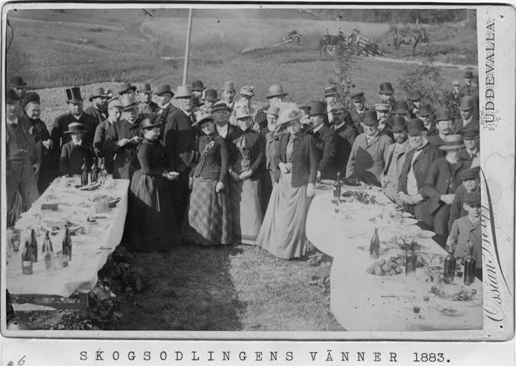 """På baksidan skrivet: """"Fotografiet taget omkr. år 1883 på Herrestadfjället vid Konsul W. Thorburns jaktstuga """"Trollgild"""" utflykt med Skogsodlingens vänner""""."""