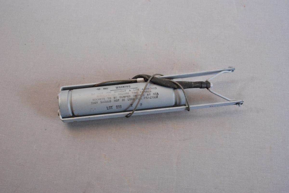 Patron til linepistol/redningspistol. Metallsylinder med feste for line i wire. Rundt wiren en hylse i vevd nylon.