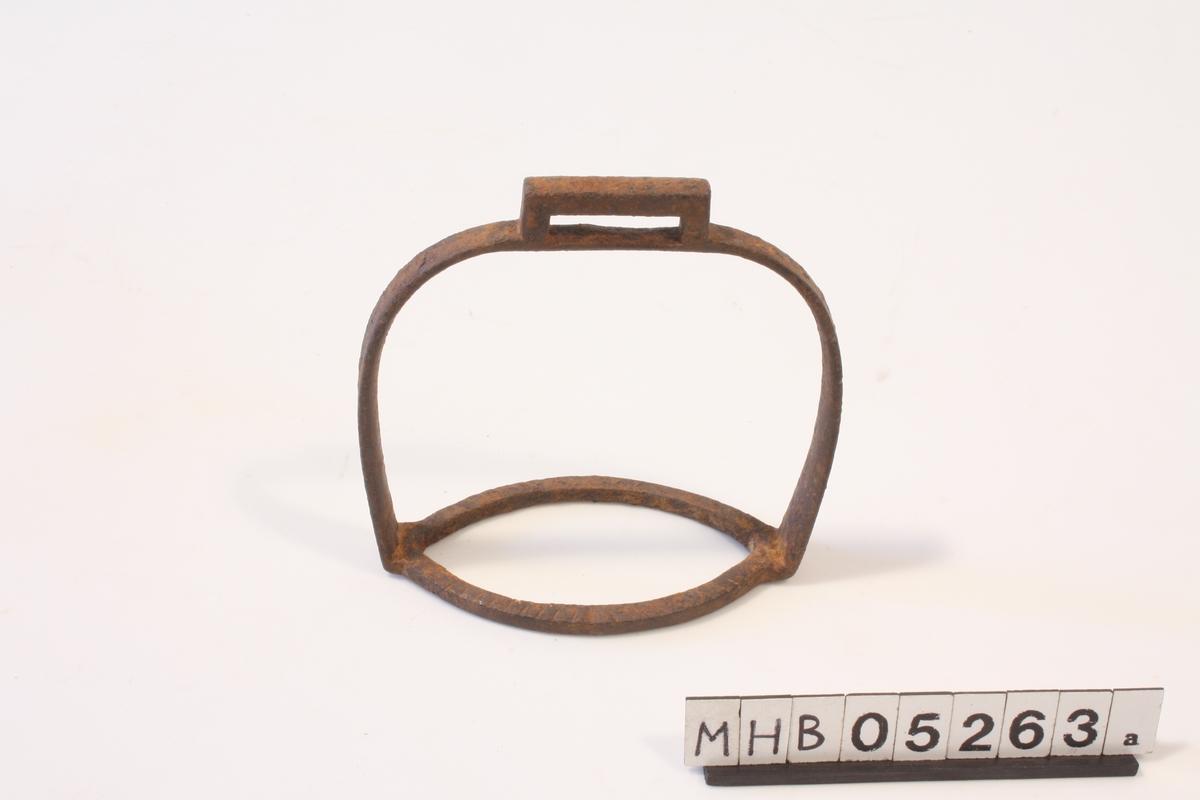 Stigbøyle av jern. Oval ring som underlag for fot. Spenne på oversiden til feste av lærreim. Ingen lærreim følger med.