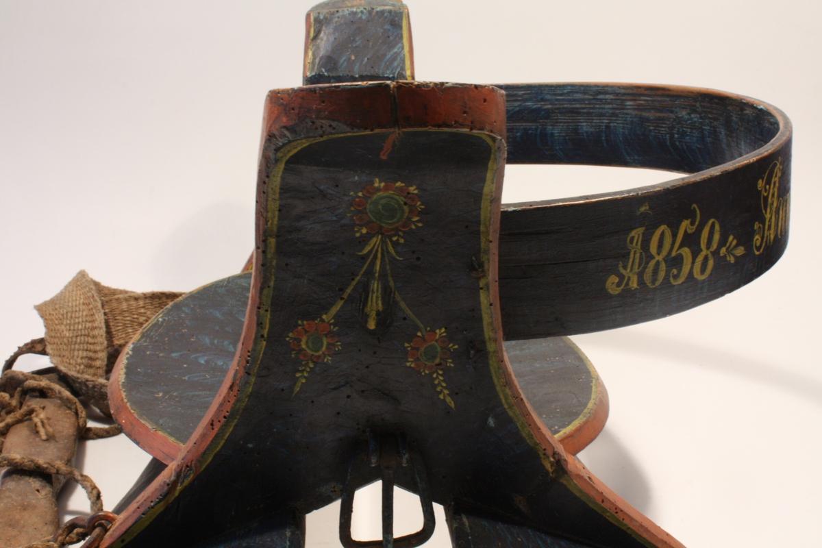 """Måla i ein myrk blå marmorering med små roser på karmane. På ryggbrettet måla med gult """"1858 Anna Torgjørnsdatter Haavik""""."""
