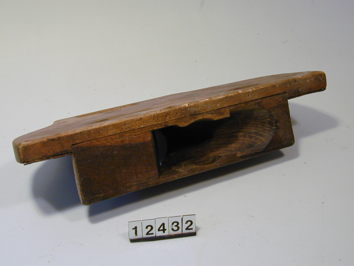 Teknikk: Skåret. Sponhus for høveljern. Forsterket med langsgående jernbånd. Høvel festet til anleggsbrettet med to jernskruer. Form: Buet såle med kraftig brett.