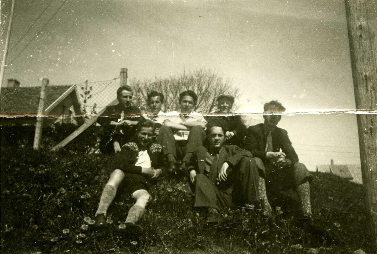 Gruppebilde fra sørøstre hjørne på Stadion. En gruppe unge menn er tilskuere til noe på Stadion. Noen av mannfolkene er kledd i knickers, andre i langbukser. De sitter henslengt i en skråning hvor det vokser løvetann. Bildet er trolig fra vår/sommer 1942.