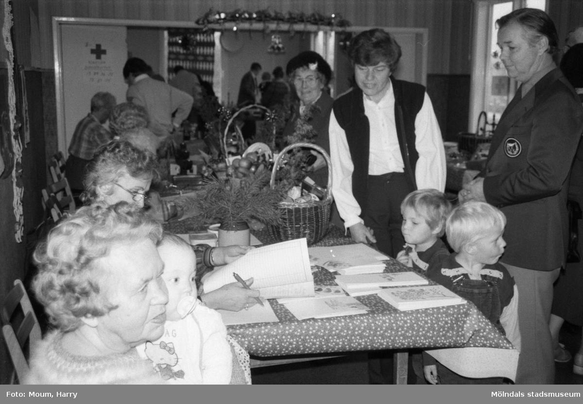 """Röda Korsets julbasar i gamla kommunalhuset i Kållered, år 1984.  Kvinnan stående till vänster är Gun-Britt Eklund med sina tvillingar, Kållered och Rolf Werner, lärare i Brattåsskolan och engagerad i RK Kållered. """"Gammal och ung trivdes på basaren i Kållered.""""  För mer information om bilden se under tilläggsinformation."""