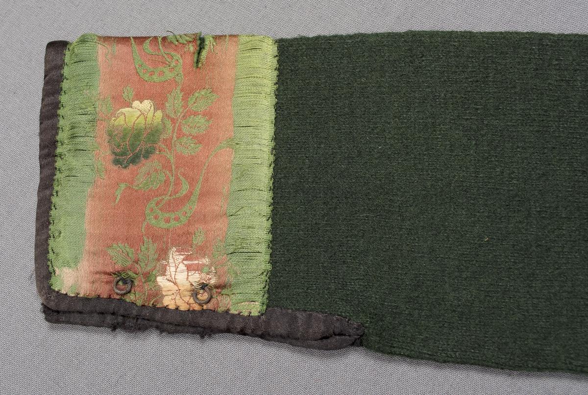 Spedetröja i grönt ullgarn. Tröjan är slätstickad med mönsterränder i nederkanten. Litet sprund i sidorna. Ärmsprundet är 90 mm långt, det hålls ihop av två hyskor och hakar, tre hakar saknas. Invändigt är halsringningen kantad med en svart- och vitmönstrad ca 15 mm bred remsa i tryckt tyg. Ärmen är kantad nedtill och längs sprundet med ett svart sidenband. Ärmen är också dekorerad med ett 60 mm brett mönstrat sidenband i rosa och grönt.Kantremsor och band är påsydda för hand. Tröjan är valkad. Masktäthet/cm: ca 7 maskor på höjden och 5,5 maskor på bredden. Axelbredd: 125 mm. Ärmlängd: 550 mm. Bredd nedtill: 325 mm. Nedtill på framstyckets högra sida har tröjan en sydd märkning med blå tråd.