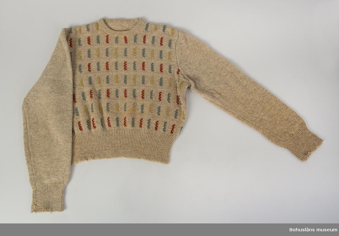 Stickad jumper i ullgarn,  naturvitt och ofärgat. Hela framstycket med mönstret Finska axet. Formgivet av Emma Jacobsson.    Hål, fläckar, missfärgningar samt lagningar. Saknar etikett.