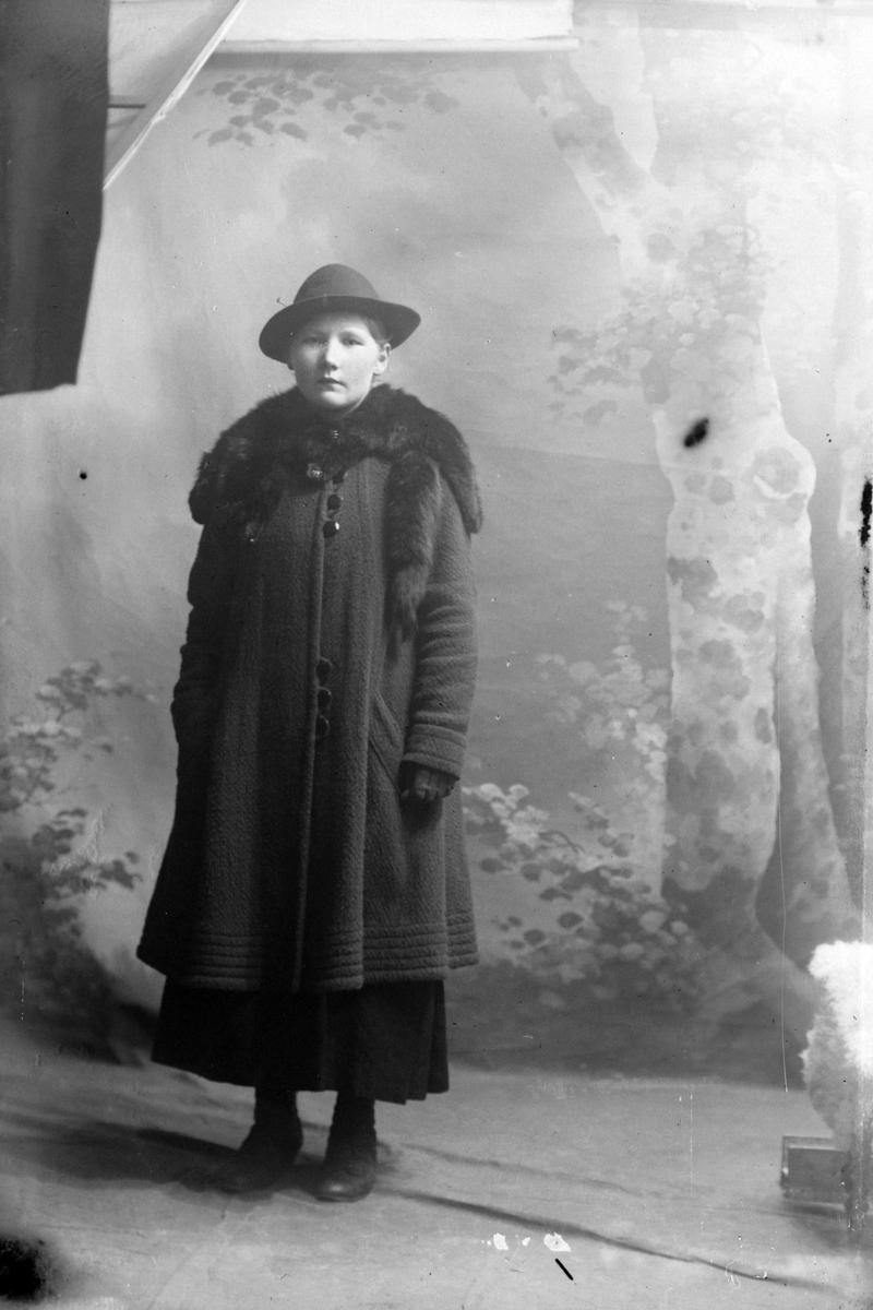 Studioportrett av en kvinne i en lang kåpe.
