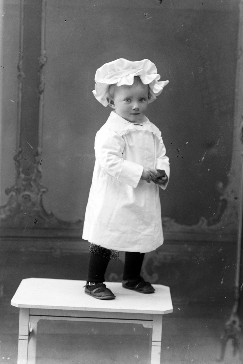 Studioportrett av et lite barn med lue på hodet.
