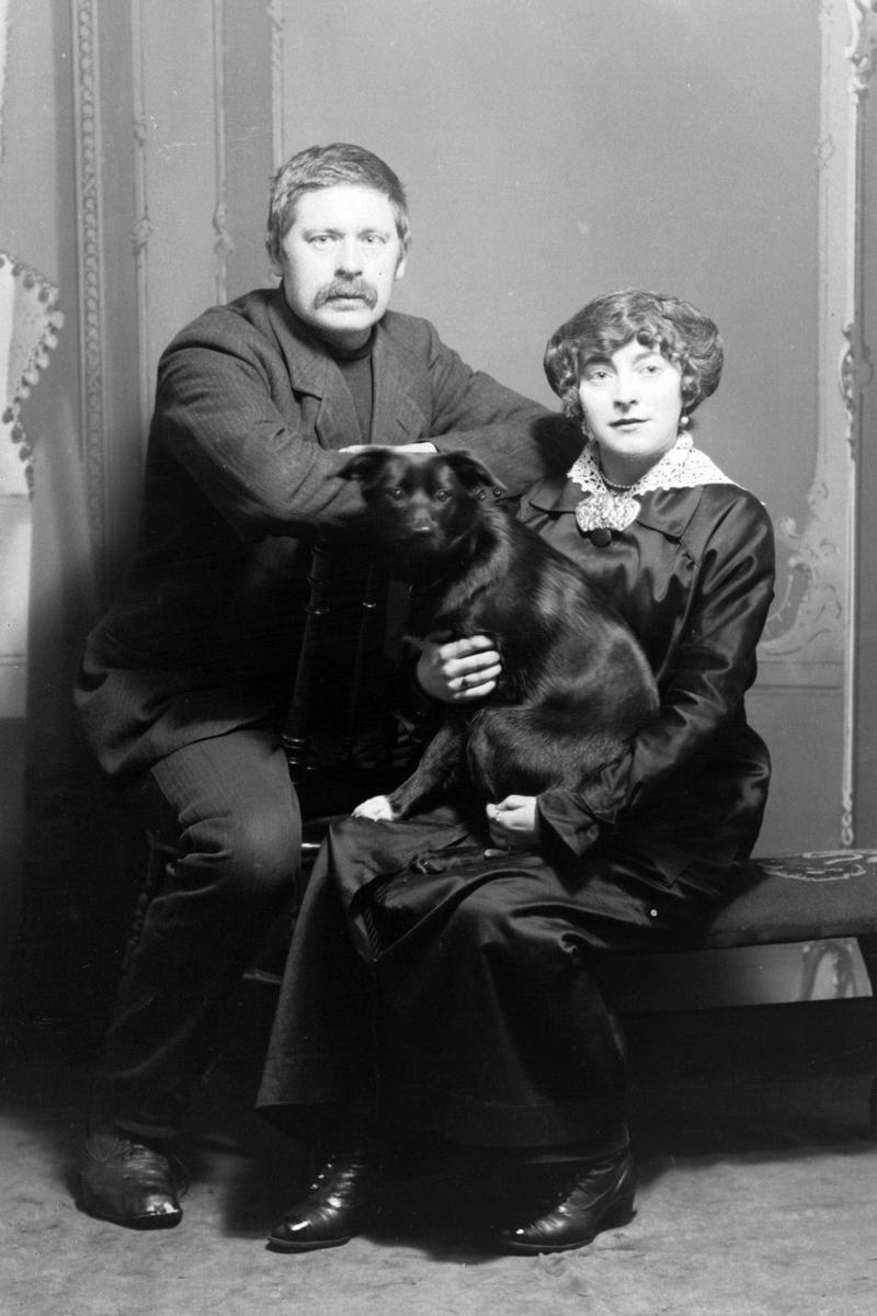 Studioportrett av to personer med en hund.