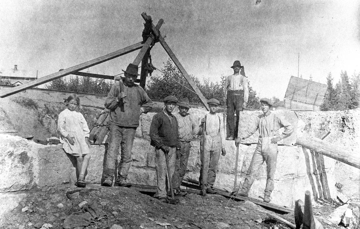 Gruppe, arbeidslag ved steinmur, 6 menn og ei jente. Jernbaneundergang ved Ådalsbruk stasjon, Løten. Muligens etablering av sidespor til Klevfos. Det private sidesporet fra Aadalsbrug stasjon til Klevfos ble tatt i bruk i 1895. Fire år senere bygde Aadals Brug sitt eget sidespor fra Klevfos-sporet og opp til fabrikken sin. FRA VENSTRE: MAY BRYHNI, OLE OLSEN, PEDER GAUSTAD, KRISTIAN NORDBY, BAK: MAGNUS BAKKE, IVAR FRANTSEN