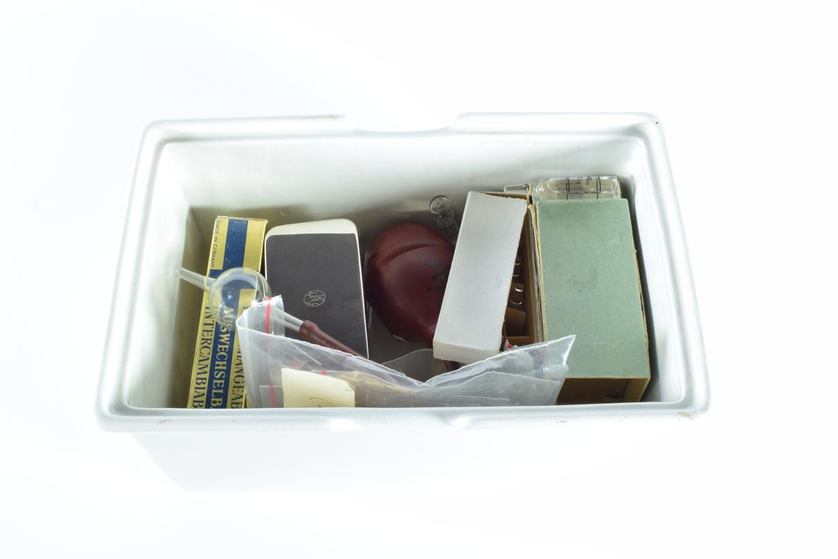 """Skrin med lokk i hvit porselen. Skrinet inneholder diverse gjenstander brukt i apotekvirksomhet.  Skrinnet inneholder:  1 grønn eske med """"Sterilpakning for kanyler"""". I esken ligger det 13 små rør i glass og 1 i plast.  1 hvit eske med 8 ampuller med Dolormin til injeksjon.  2 uåpnede pakker med sprøyter, produsert i Tyskland. Eskene er dekorert med et blått kors på en gullfarget bakgrunn og en logo som viser et hus og bostaven H.  2 kvadratiske metallbokser med sprøyter. På lokket til en av boksene er det en logo som viser et hus og bokstaven H.  1 pose med seks munnstykker til nesespylere.  1 lite knivblad med tager og bokstavene A L.  1 pose med flere små stålrør med et lite dråpeformet """"håndtak"""" i en ende.  1 liten pumpe i rød gummi."""
