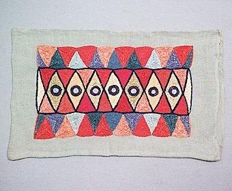 Broderat litet kuddvar sytt i ljusgrått linne. Tätt broderi, som täcker kuddens rektangulära mittfält, i form av trianglar och romber samt en rad med cirklar mitt på. Broderiet är utfört i schattersöm och kedjesöm i två nyanser rött och gult samt blått, orange och gult.Mönstret är typiskt för 1950-talet,