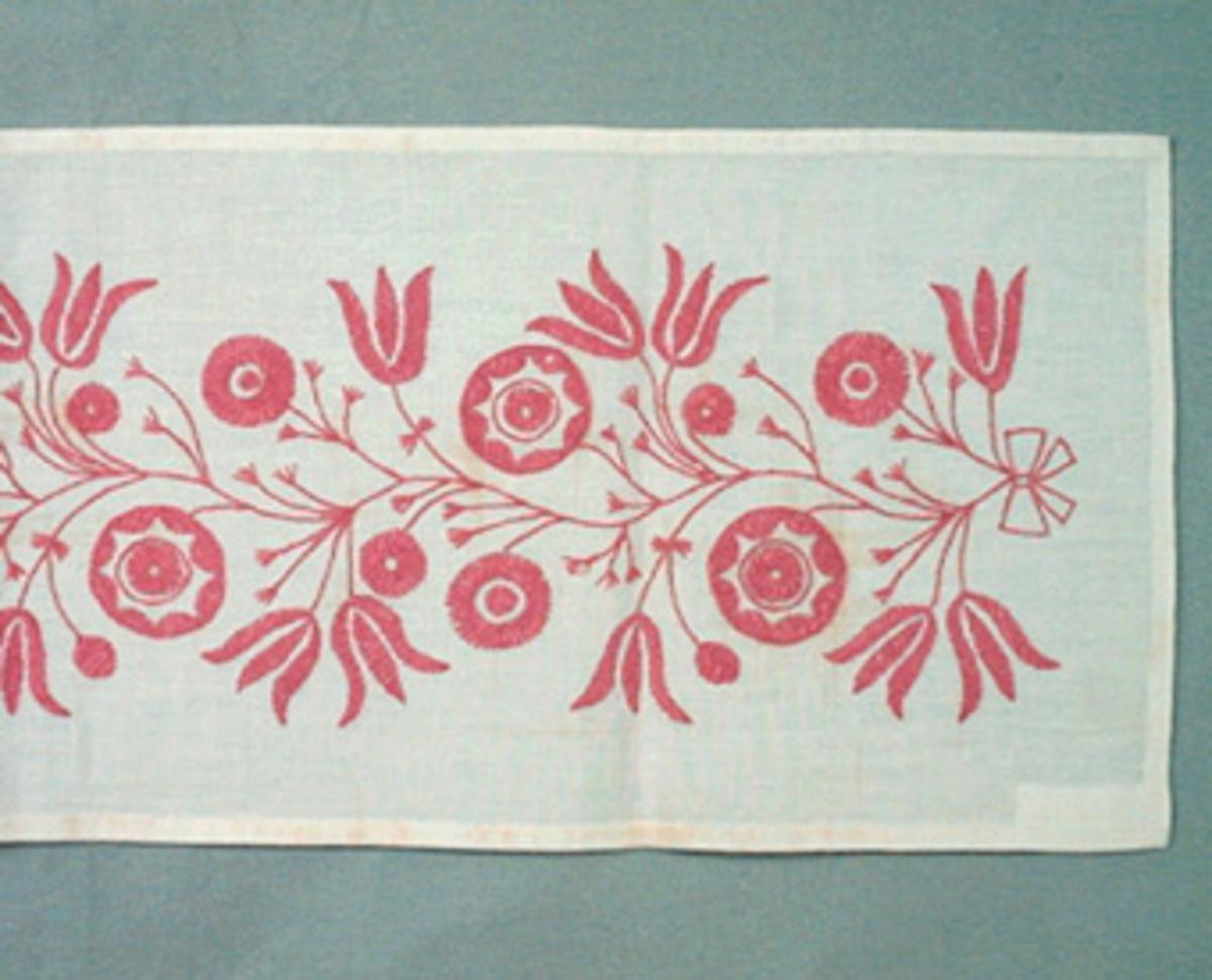 Löpare i halvblekt linne broderad i Melpasöm med rosa garn, 1 lintråd och 1 tråd av bomullsgarn. En bred slinga med runda och klockformade blommor i flätsöm på kvistar i stjälkstygn med blad i tofssöm. Detaljerad materialbeskrivning finns i Broderiregistret.