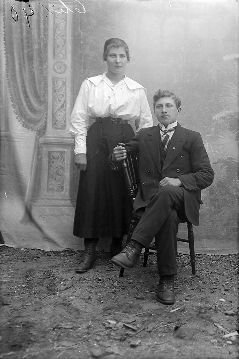 Portrett. Par i 20-åra. Mannen sitter, kvinnen står ved siden.Bildet er tatt i Glomfjord, Meløy.