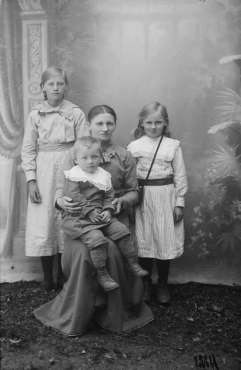 Portrett. Kvinne med 3 barn. Kvinnen sitter med minstebarnet på fanget. Kvinnen er i 30-åra. De tre barna, en gutt og to jenter er i alderen ca. 3-12 år.