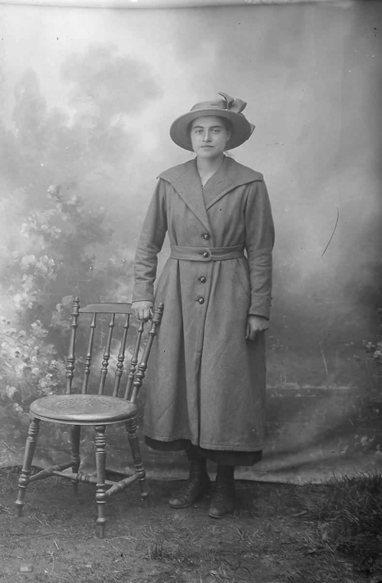 Portrett. Dame, står og støtter til en pinnestol. Hun har på seg frakk med belte og hatt.Bildet er tatt i Sørfold.