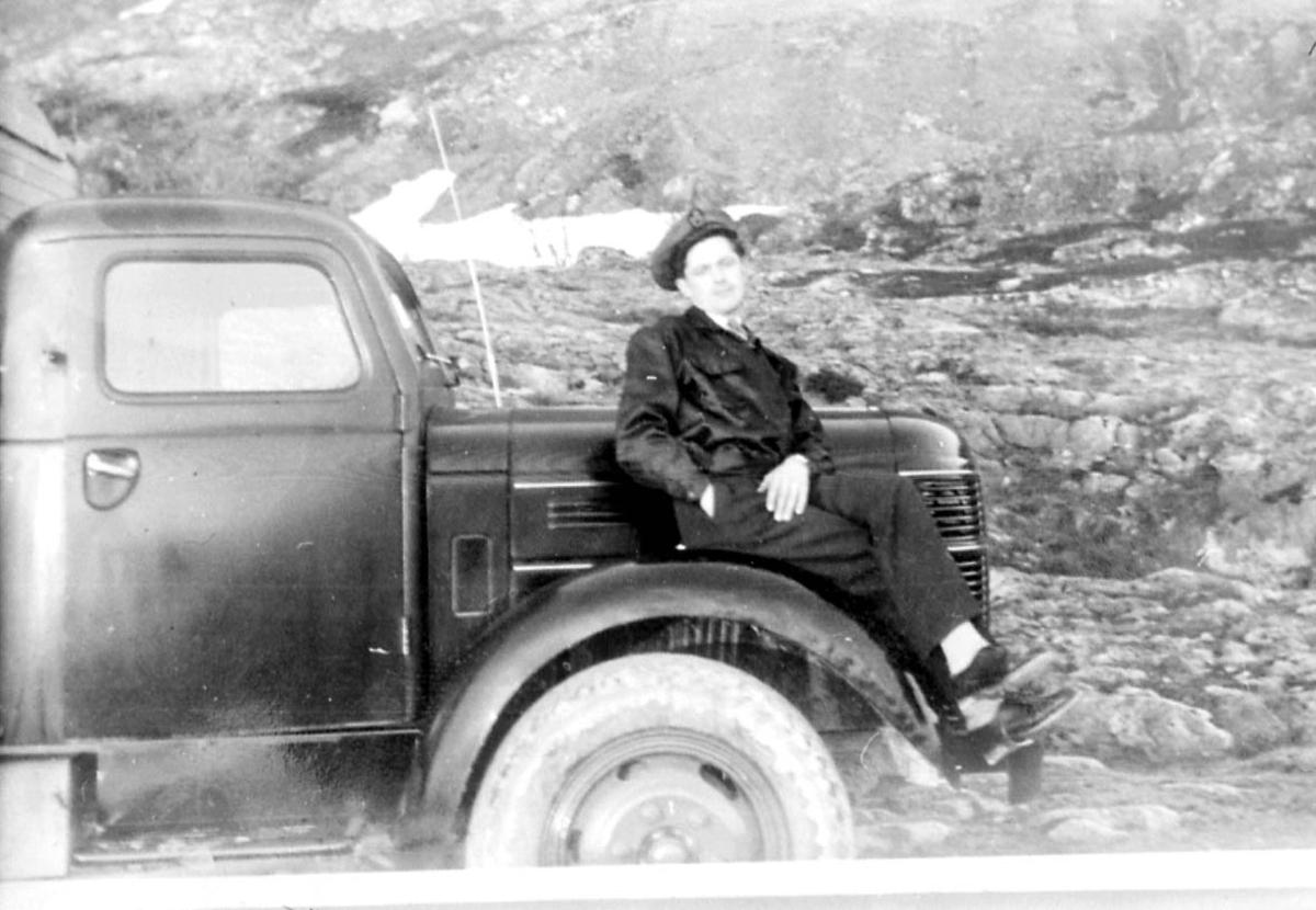 Portrett. 1 person, mann i militæruniform sitter på panseret til en lastebil - kjøretøy.