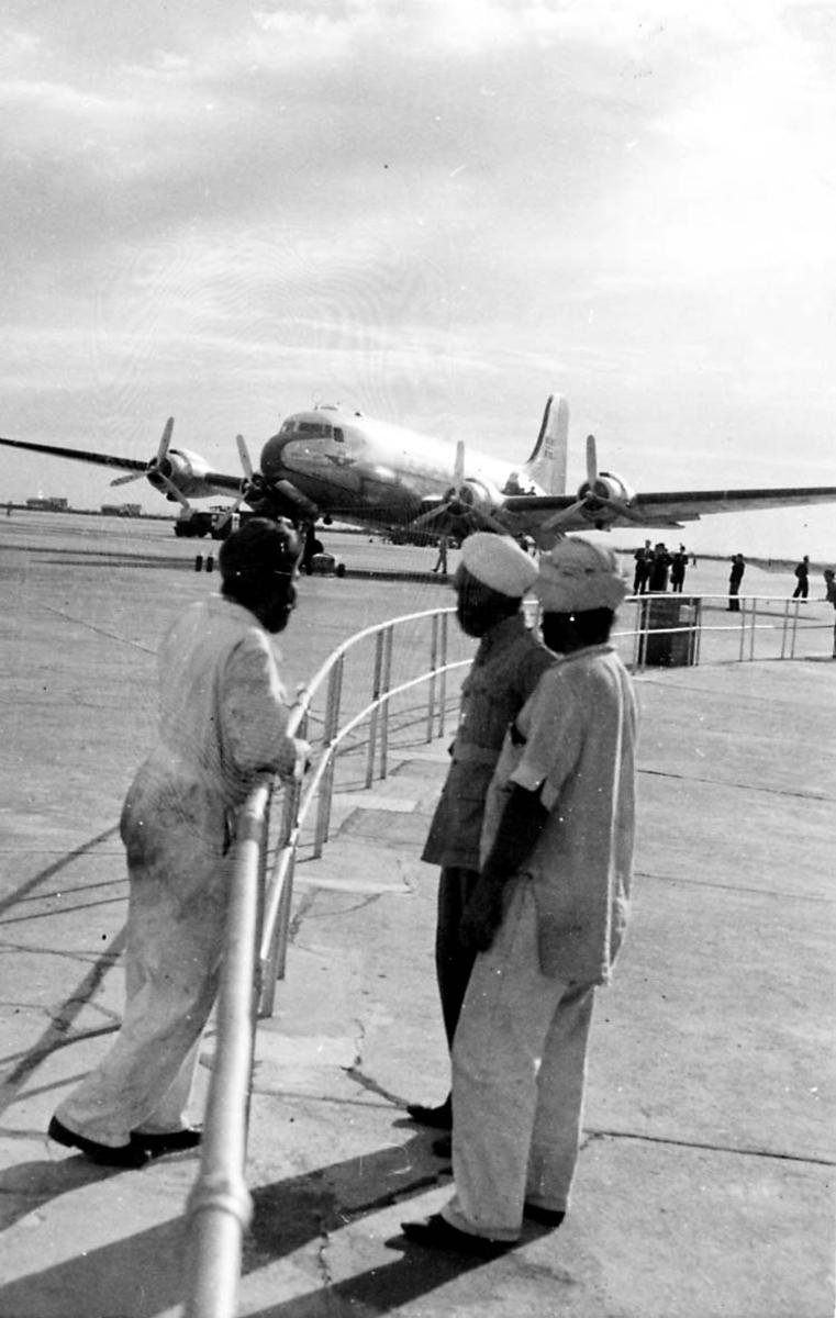 Lufthavn. 1fly på bakken DC-4 Douglas C54 Skymaster. Noen personer i fogrunnen.