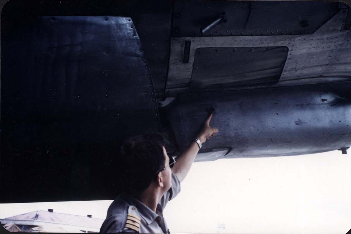 Lufthavn. 1 fly på bakken med skader. Portrett, 1 person peker på kulehull.