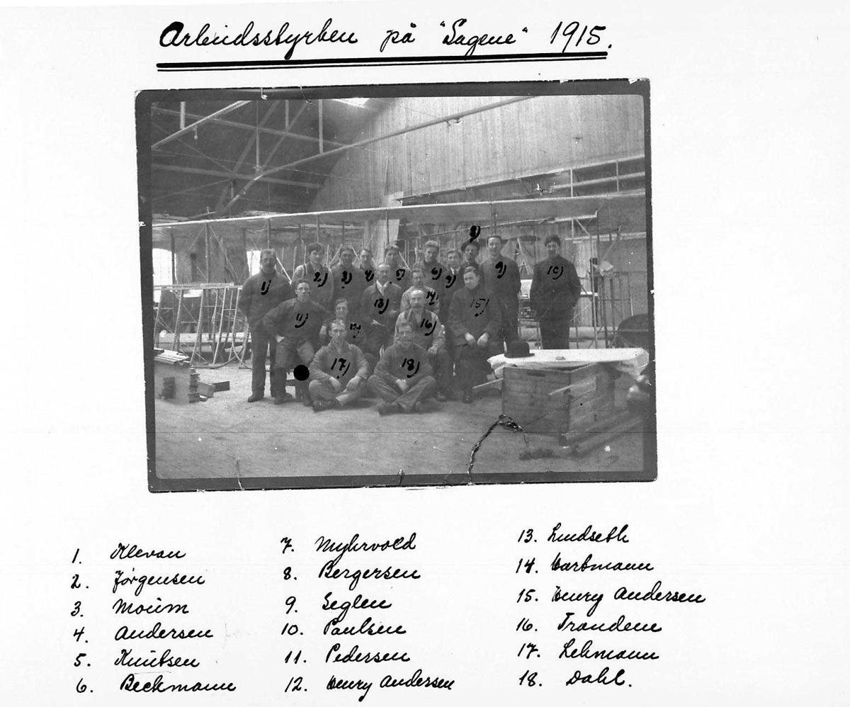 Flyfabrikk. Gruppefoto av ansatte foran ett fly. Tatt inne i fabrikken.