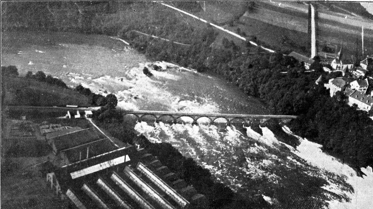 Utklipp: Luftfoto større elv - fossefall. Ei bru over elva og en del bygninger på begge sider.