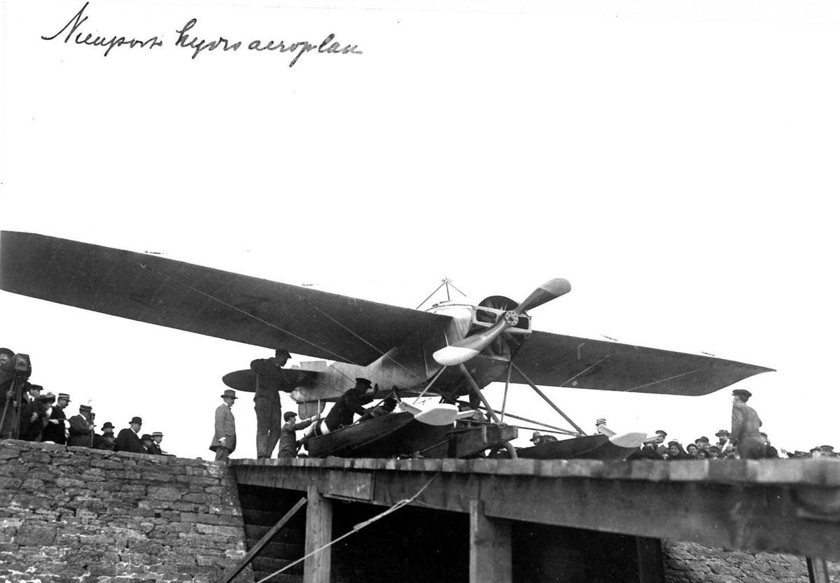 Ett fly på ei kai, Nieuport. Flere personer ved flyet.