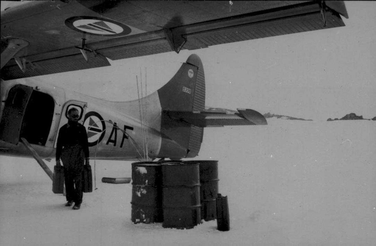 Ett fly på isen, Otter OAF. En person bærer på to bensinkanner. Noen bensingfat ved flyet.