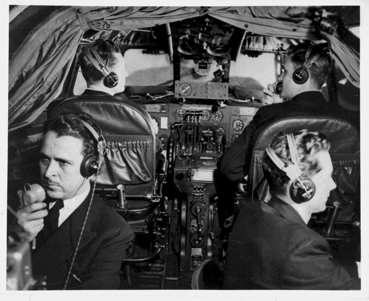 Fra cockpiten til en Boeing 314 Clipper. Tre personer, menn, i cockpiten.